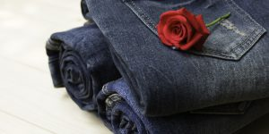 Blue jeans folded with red rose on wooden table and on wooden background.