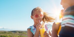 Children drinking orange juice outdoor